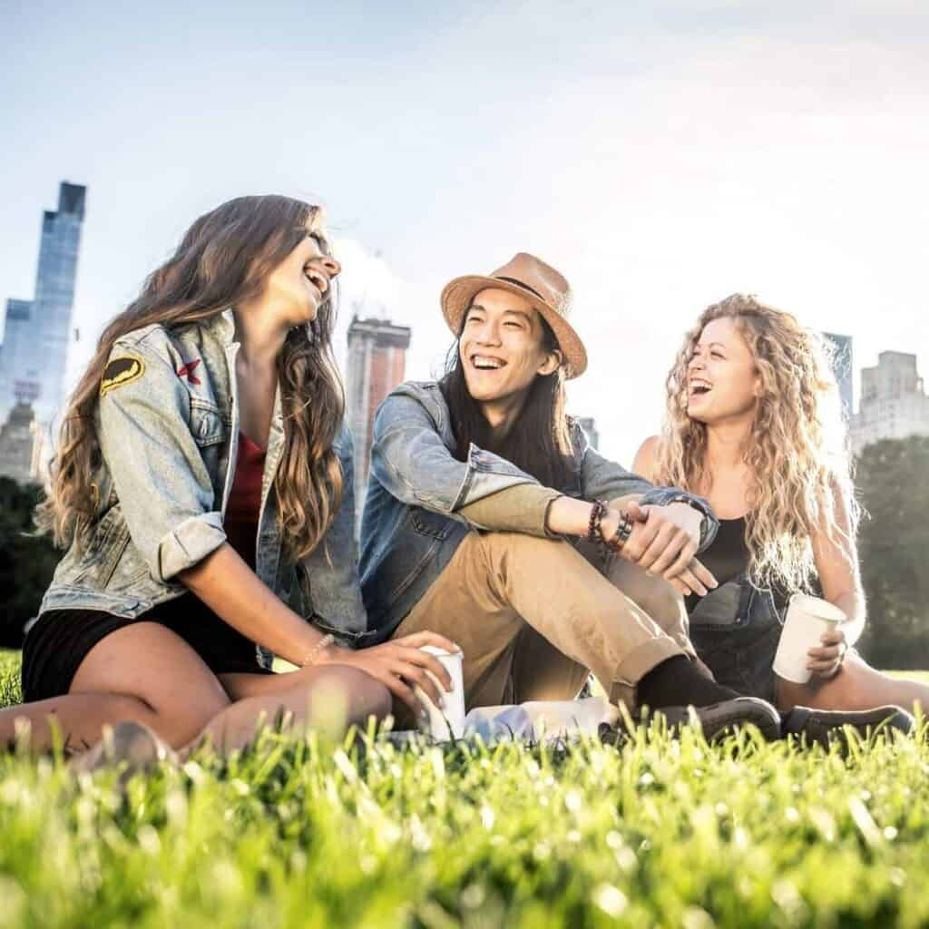 Three friends sitting on grass and laughing.